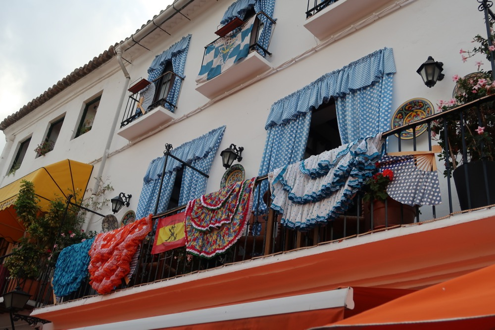 De balkons in het pitoreske Marbella hebben veel bloemen en dit balkon laat Spaanse kleden zien